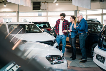 Car dealer showing cars to couple in showroom