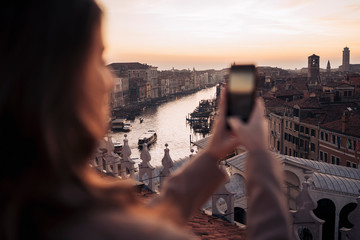 Young woman taking cell phone picture on a balcony above the city of Venice, Italy