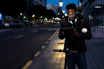 Man in the city at night with tablet and e-scooter