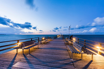 Germany,?Mecklenburg-Western Pomerania, Prerow, Illuminated pier at dusk with clear line of horizon over Baltic Sea in background