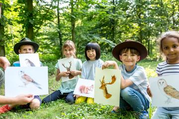 School children doung nature studies, holding pictures of animals