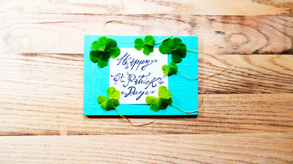 St. Patrick's Day word text with clover shamrock leafs around lucky plant on a wooden background template image photo picture