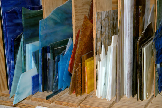 In a stain glass studio, sheets of glass are separated by hue.