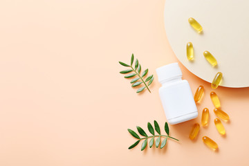 Fish oil vitamin capsules on light color background