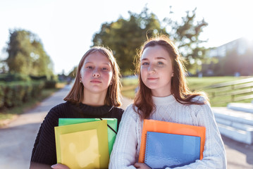 Two girls schoolgirl girlfriends 12-14 years old, summer portrait in city on street, in hands of notebooks folders textbooks, resting after school in college break. Emotions of positive pleasure.