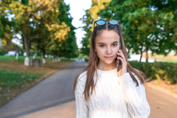 Teen girl 10-12 years old, holds smartphone in hand, listens calls on phone, in summer on street in park, beautiful and sincere. The concept of call to parents. Free space for copy text.