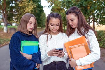 Three teenage girls schoolgirls 12-14 years old, summer city, hand smartphone, online Internet, social networks, watching photos Internet. Break school college. In hands notebooks folders textbooks.