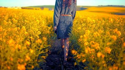Keuken foto achterwand Weide, Moeras Jeune femme de dos qui marche dans un champs de fleurs jaunes