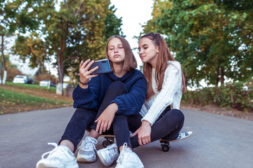 Two girls schoolgirls 12-14 years old, in summer in a city park, watch videos on a smartphone, sit on a skateboard, casual wear, a break in school and college, online official networks on Internet.