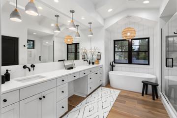 Beautiful bathroom in luxury home with double vanity, bathtub, mirror, sinks, shower, and hardwood floor