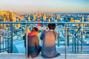 Romantic Young Couple Sitting Together on Top of Tokyo Scyscraper and Making Smartphone Pictures of The City with Tokyo Tower in Background.
