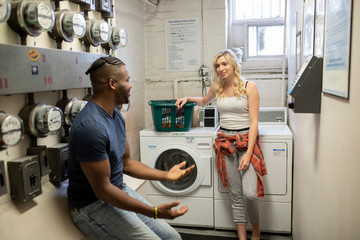 Young man and woman talking in apartment laundry room