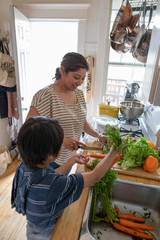 Mother and son preparing vegetables in apartment kitchen