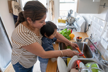 Mother and son washing carrots at kitchen sink