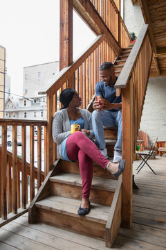 Young couple talking and drinking coffee on apartment balcony stairs