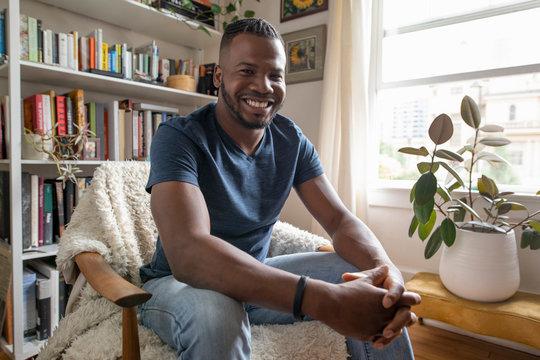 Portrait happy, confident man in apartment living room