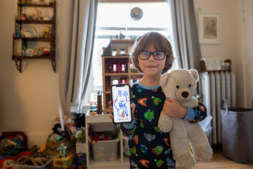 Portrait cute boy in pajamas with teddy bear showing drawing on smart phone