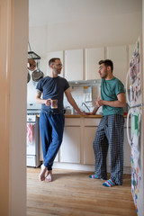 Gay couple in pajamas talking and drinking coffee in apartment kitchen