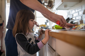 Daughter watching father washing dishes at kitchen sink