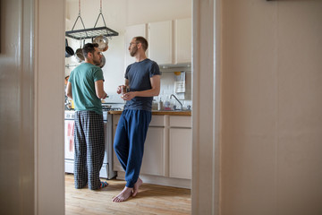 Gay couple in pajamas talking and preparing breakfast in apartment kitchen