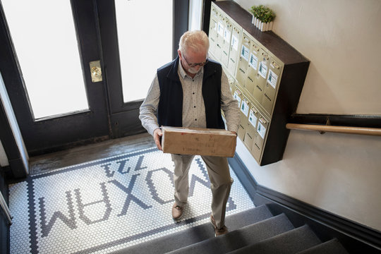 Senior man with package climbing apartment stairs