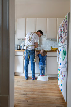 Father and cute toddler son on step stool in apartment kitchen
