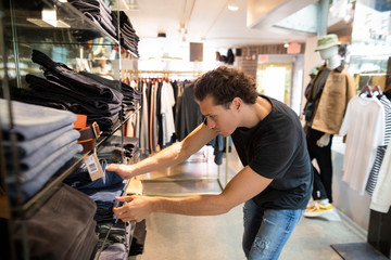 Young man choosing pair of jeans from shelf in fashion store Wall mural