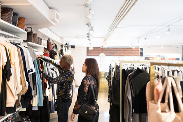 Two women looking at clothes in fashion boutique