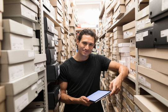 Portrait of shoe store manager in storeroom with digital tablet