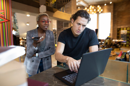 Shoe store assistant using laptop with manager holding smart phone