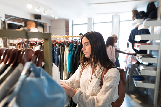 Young woman choosing clothing from rail in clothes store