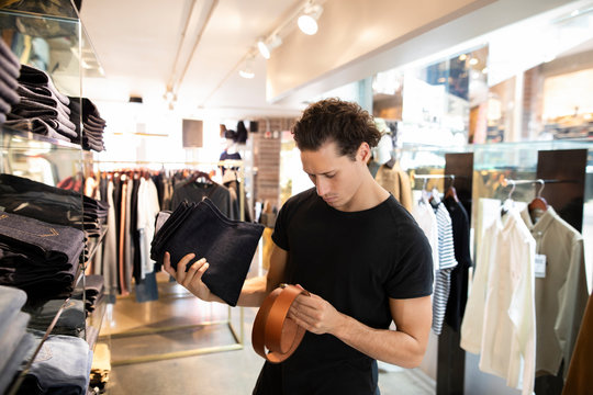 Young man choosing belt and jeans in fashion store