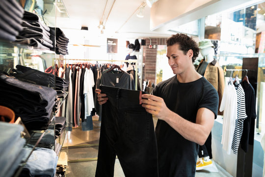 Young man choosing pair of jeans in fashion store