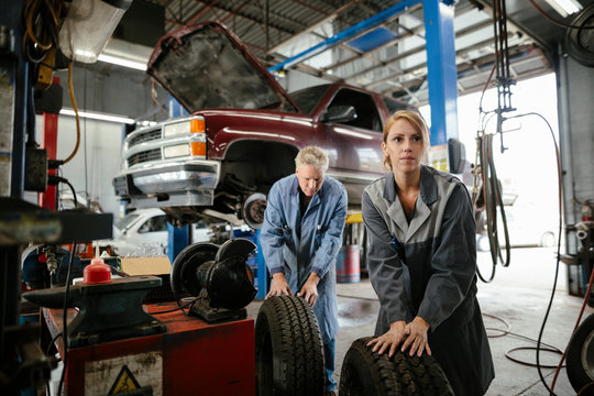 Female mechanic rolling tire in garage with employer