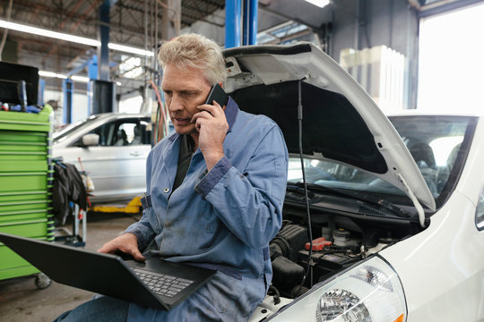 Mechanic sitting on car hood using laptop with smart phone