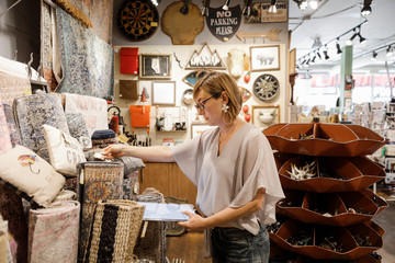 Small business owner checking rugs in interiors shop
