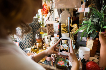 Young woman taking photo of merchandise in gift shop on smart phone