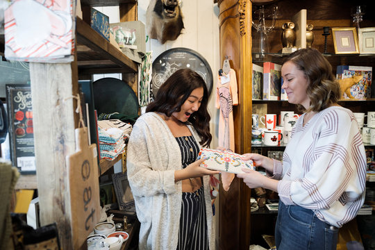 Young woman choosing gift for friend in gift shop