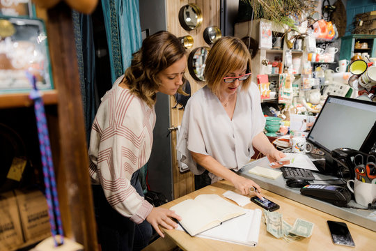 Small business owner discussing finances with colleague in gift shop