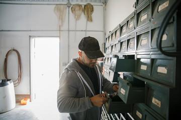 Male farmer looking inside tool bins in workshop