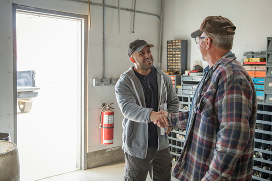 Male farmer and delivery man shaking hands in workshop