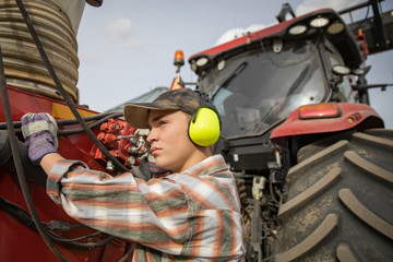 Teenage boy farmer with ear protectors standing at tractor, operating machinery