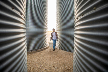 Teenage boy farmer carrying bucket between silos
