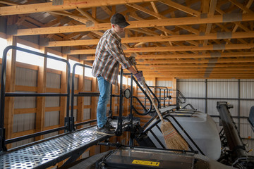 Teenage boy farmer using broom, sweeping equipment inside barn