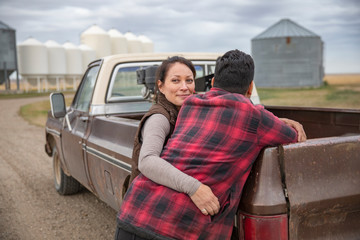 Happy, affectionate farmer couple hugging at pickup truck on farm