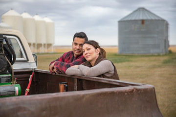 Happy, affectionate farmer couple at pickup truck on farm
