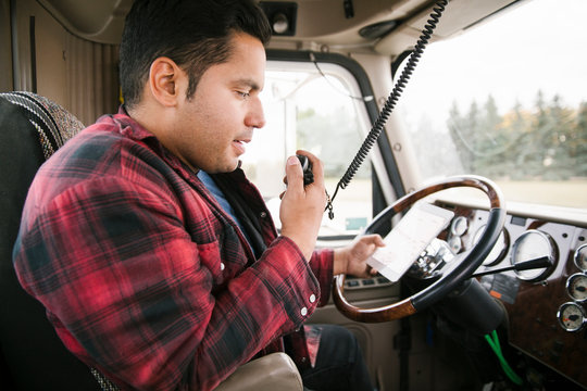 Male farmer with digital tablet talking on CB radio inside semi truck