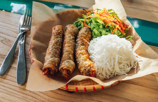 Traditional vietnamese fried spring rolls or nems served with salad and noodle. Selective focus