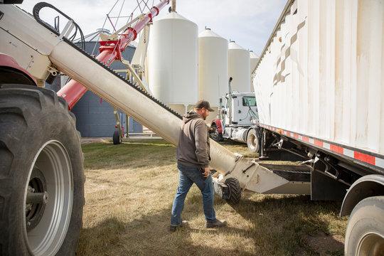 Male farmer operating grain auger on sunny farm