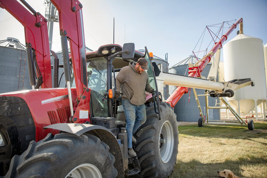 Male farmer climbing out of tractor on sunny farm